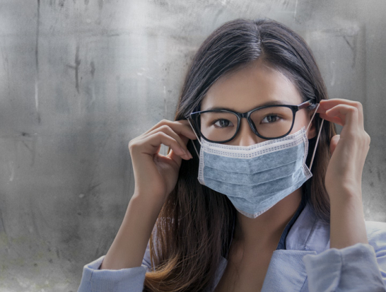Žena nosi masku za lice i leće s prozirnim naočalama zahvaljujući optifog premazu leća.